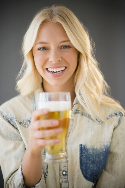 virtual happy hour ideas -  Portrait of young woman holding glass of beer, Jersey City, New Jersey, USA