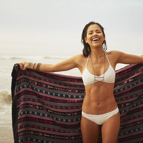 Portrait of young woman holding up blanket on beach, San Diego, California, USA