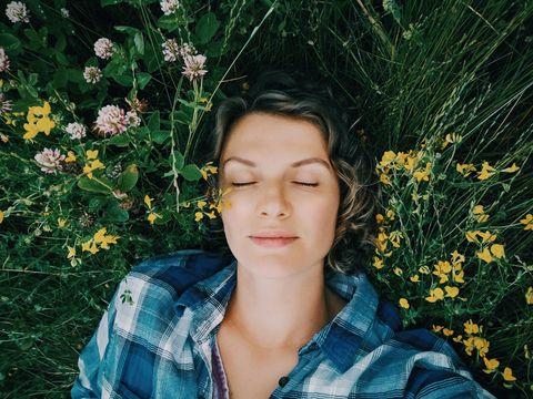 una mujer posa con una camisa de cuadros tumbada sobre unas plantas y flores