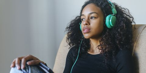 Portrait of young woman sitting in armchair listening music with headphones and tablet