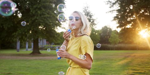 Portrait of young woman wearing yellow dress blowing bubbles in park at sunset