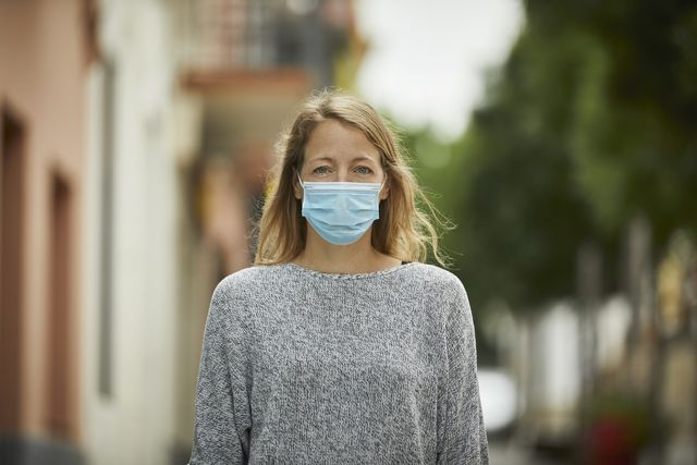 portrait of young woman with face mask on the street