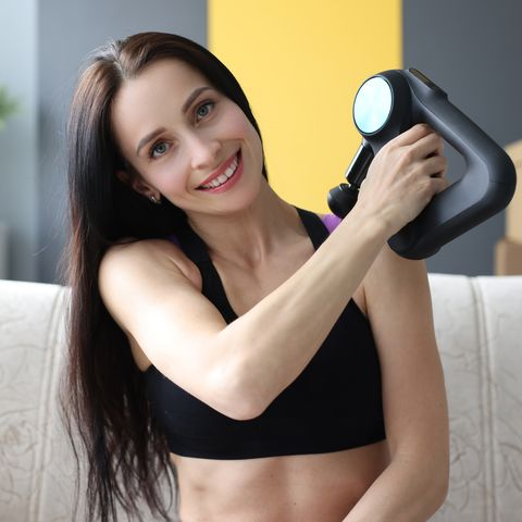 portrait of young woman with percussion massager in her hands at home