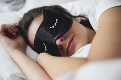 Portrait of young woman with sleep mask in bed