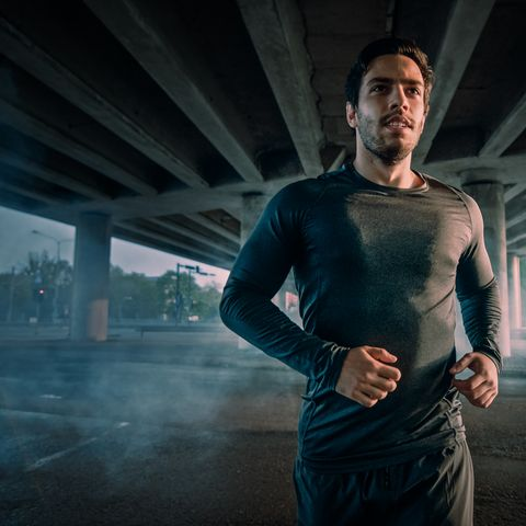 Portrait Shot of an Athletic Muscular Young Man in Sports Outfit Jogging in the Street. He is Running in an Urban Environment Under a Bridge.