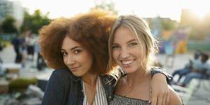Portrait smiling, confident young women friends hugging in park