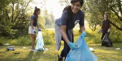 Smiling woman volunteering, cleaning up garbage in park