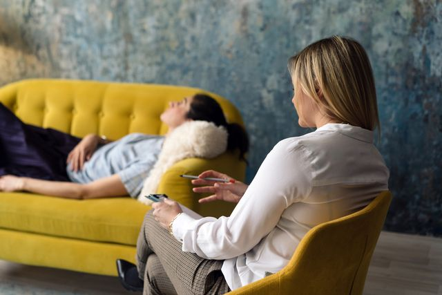 positive blonde middleaged woman psychologist talking to girl patient