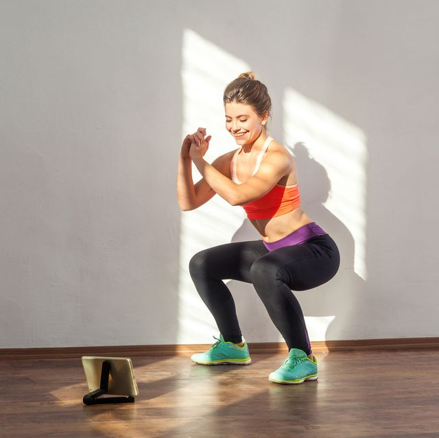 positive sportive woman with bun hairstyle and in tight sportswear doing squatting indoor studio shot illuminated by sunlight from window