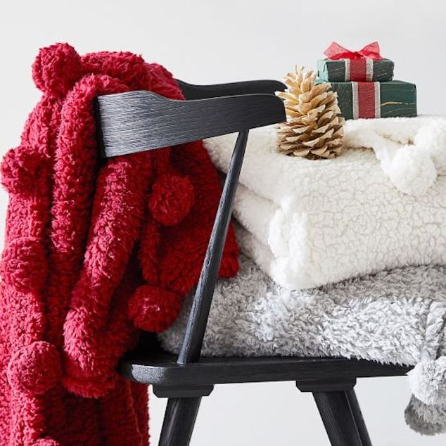 blankets with poms and wreath hanging over manetl with chirstmas tree toppers and a present