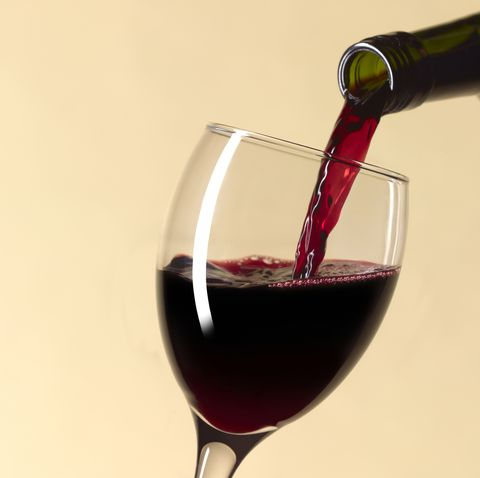 Pouring glass of red wine with copy space