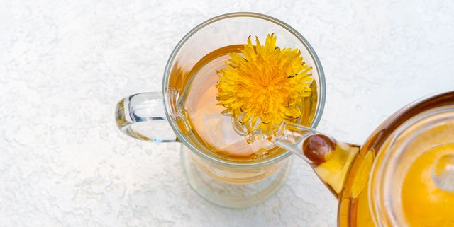 pouring herbal dandelion tea into a transparent cup from a teapot on a white background, copy space, close up