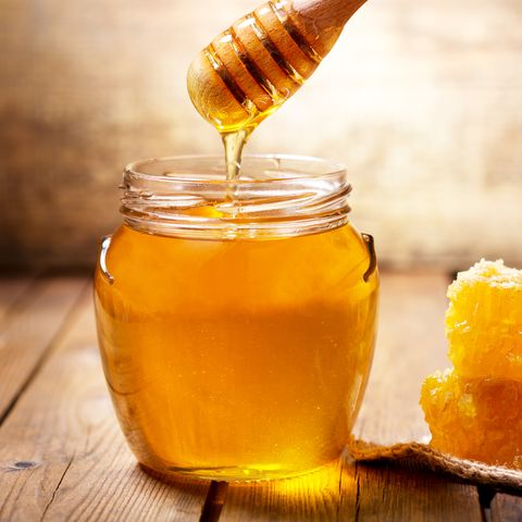 pouring honey into jar of honey