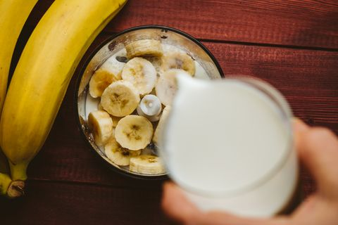Pouring milk in blender over pieces of bananas, banana smoothie, top view