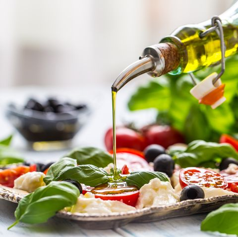 Pouring olive oil on caprese salad. Healthy italian or mediterranean meal