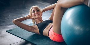 "Fighting diet!Woman exercising on ball .Attractive builder muscles women looking camera in fitness gym""n"