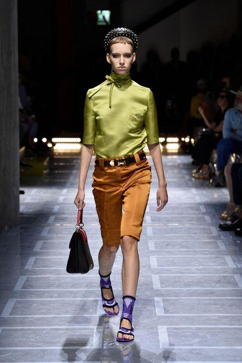 Fashion model, Fashion show, Fashion, Runway, Clothing, Fashion design, Yellow, Footwear, Shorts, Street fashion,