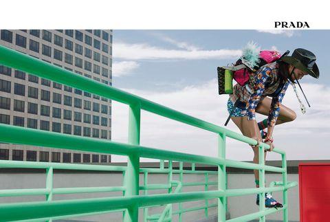 Human leg, Metropolitan area, Helmet, Tower block, Bag, Knee, Metropolis, Street fashion, Commercial building, Handrail,