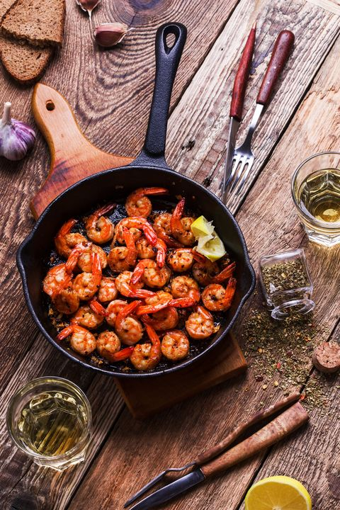 prawns in frying pan  and two glasses white wine