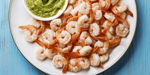 prawns shrimps with guacamole fresh dip on plate on blue background
