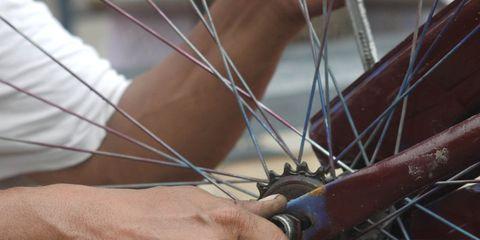 A cyclist checking his bike wheel.