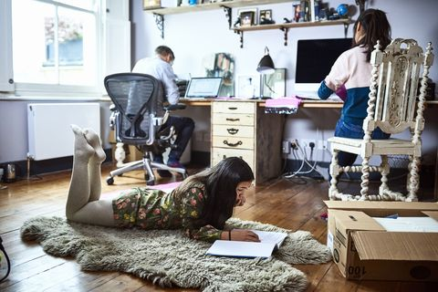 pre teen girl lying in parent's home office during school holidays and reading