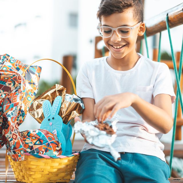 boy sitting on playground with easter basket