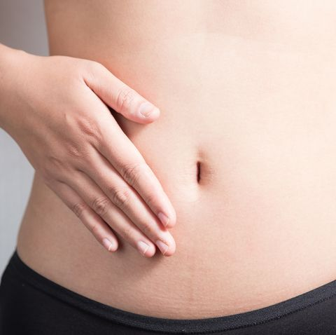 pregnancy or diet concept, female hands protecting the stomach on white background