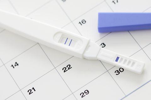 pregnancy test showing positive result and calendar