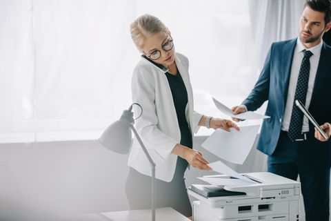 pregnant businesswoman talking on smartphone while using printer and businessman with papers standing behind in office