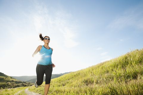 Pregnant Hispanic woman running in remote area
