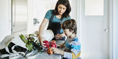 pregnant mother showing young son apples in kitchen after shopping for groceries