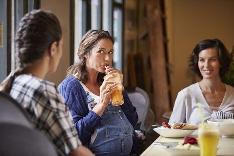 una mujer embarazada bebe con pajita un batido de frutas