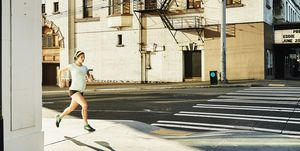 Pregnant woman running on city sidewalk during early morning workout