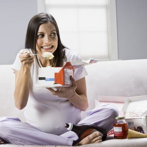 pregnant woman sitting on a couch and eating ice cream