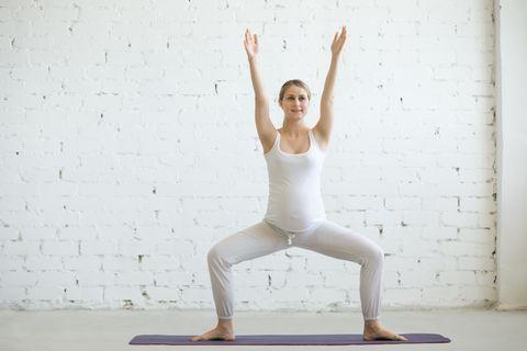 Pregnant young woman doing prenatal yoga. Sumo Squat Pose