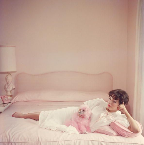 joan collins relaxes on a bed