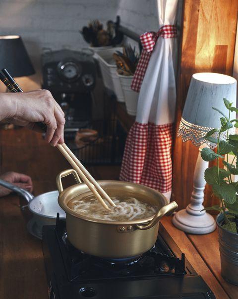 preparing vegan stir fry udon noodles with vegetables