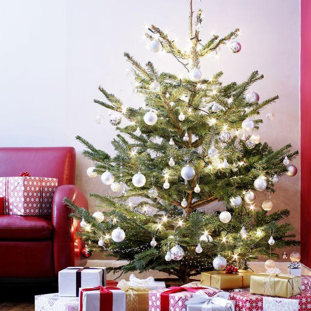 presents surrounding illuminated christmas tree in living room