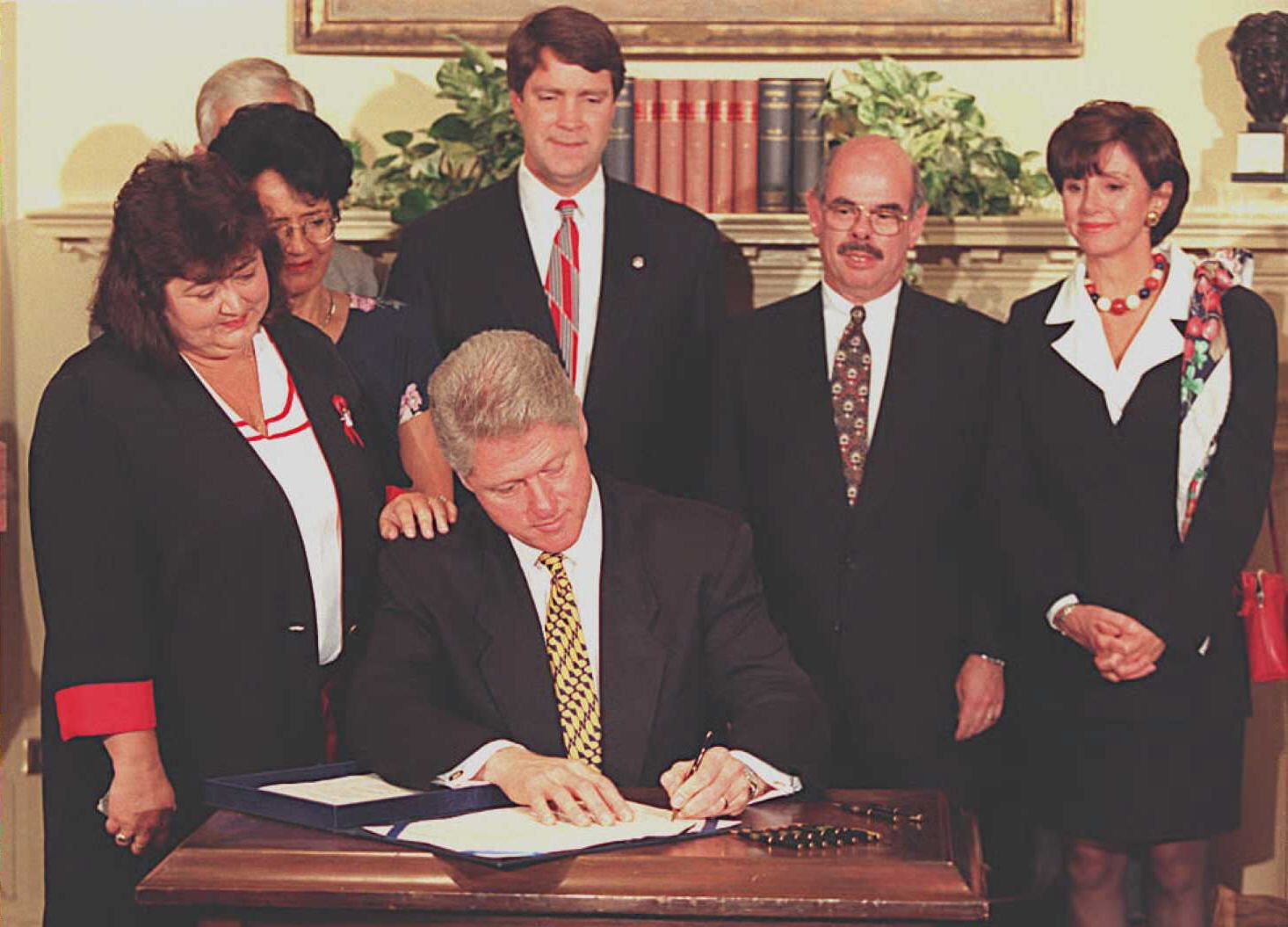 Pelosi watches as President Bill Clinton signs the Ryan White Comprehensive AIDS Resources Emergency Act Amendments of 1996.