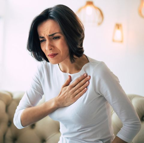 closeup photo of a stressed woman who is suffering from a chest pain and touching her heart area