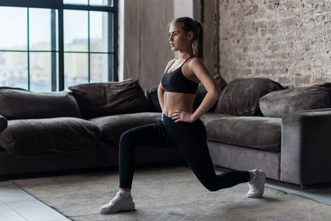 pretty fit woman doing frontal lunges or squat exercise indoors in a flat