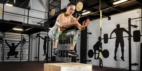 Pretty fit woman jumping on wooden crate training concept