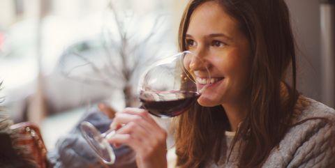 Pretty happy woman drinking wine