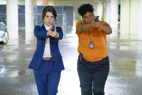 meredith macneill y adrienne c moore, caracterizadas como las agentes samantha y kelly, sus personajes en pretty hard cases, apuntan al frente con sus pistolas