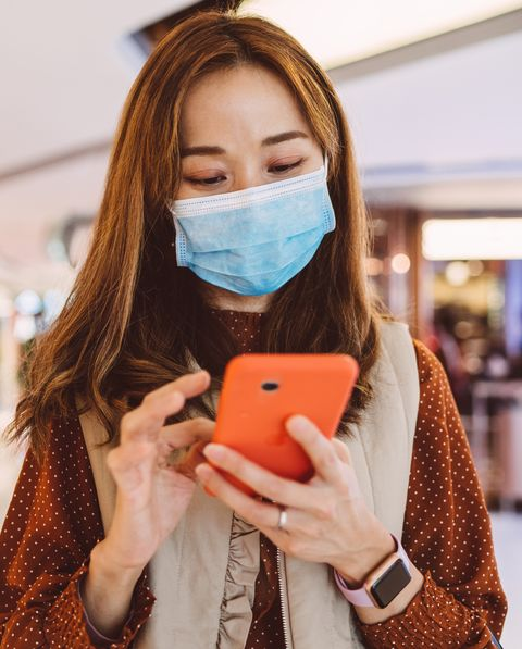 pretty young lady in medical face mask using smartphone in mall