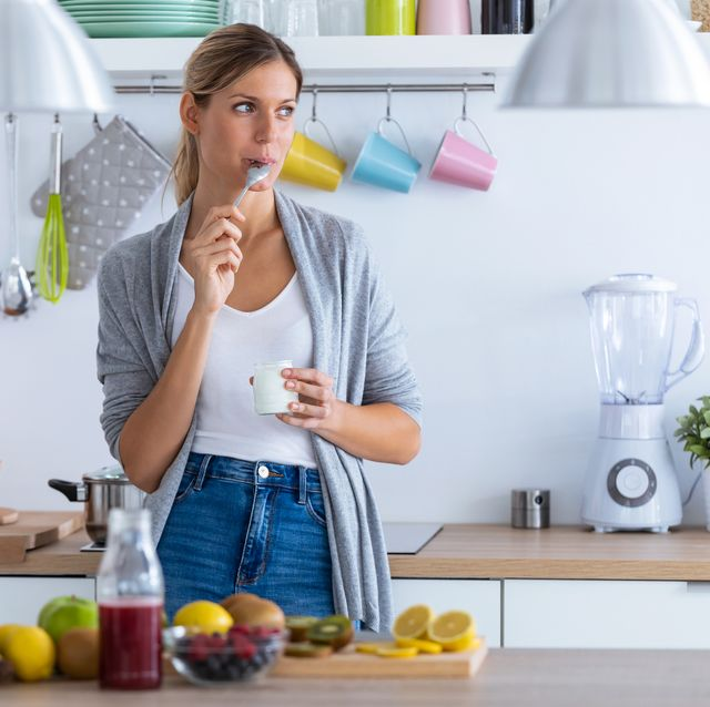 pretty young woman eating yogurt while standing in the kitchen at home