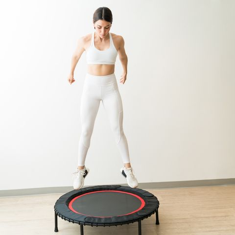 pretty young woman in white sportswear jumping on trampoline