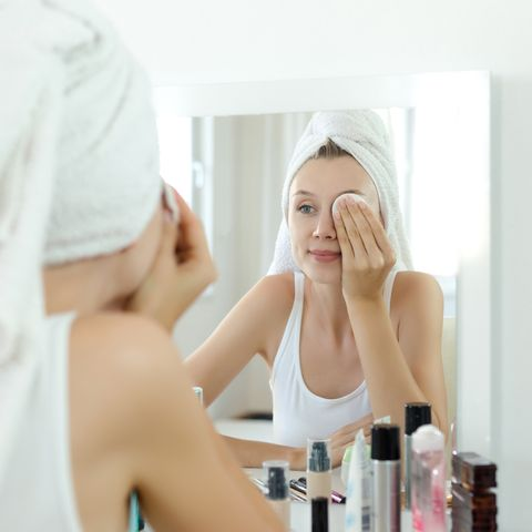 pretty young woman is cleaning her face