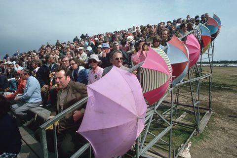 Spectators With Umbrellas in the Grandstands
